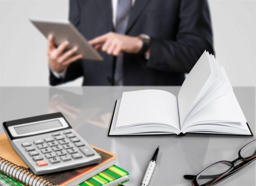 Empleado de administración con su tablet frente a un escritorio con libro y calculadora