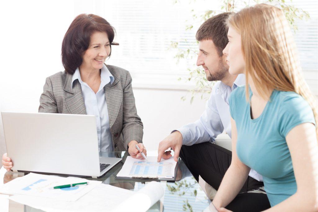 Asesora educativa sentada frente a su laptop en el escritorio ayudando a dos estudiantes