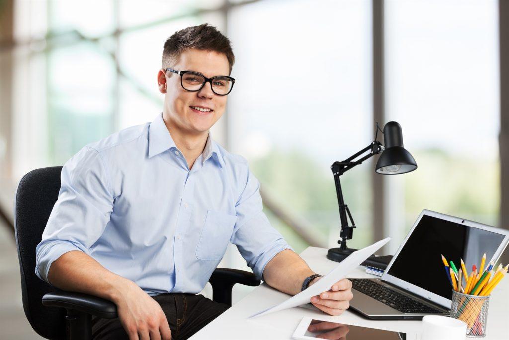 Supervisor virtual en su escritorio de casa leyendo un informe que sostiene con una mano y sonriendo