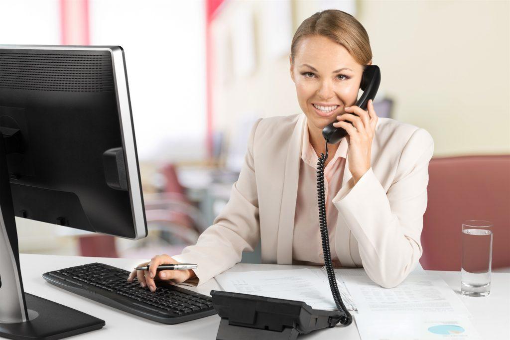 Mujer en su hogar frente a un ordenador contestando una llamada