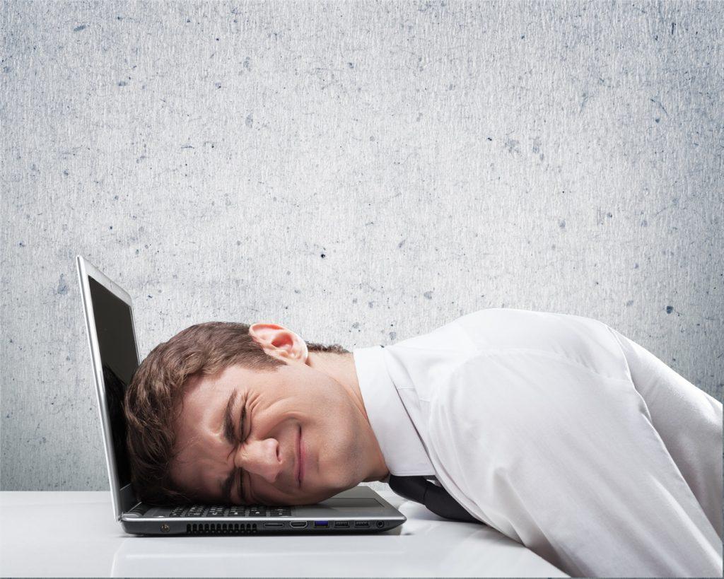 Hombre estresado apoyando su cabeza con una laptop abierta