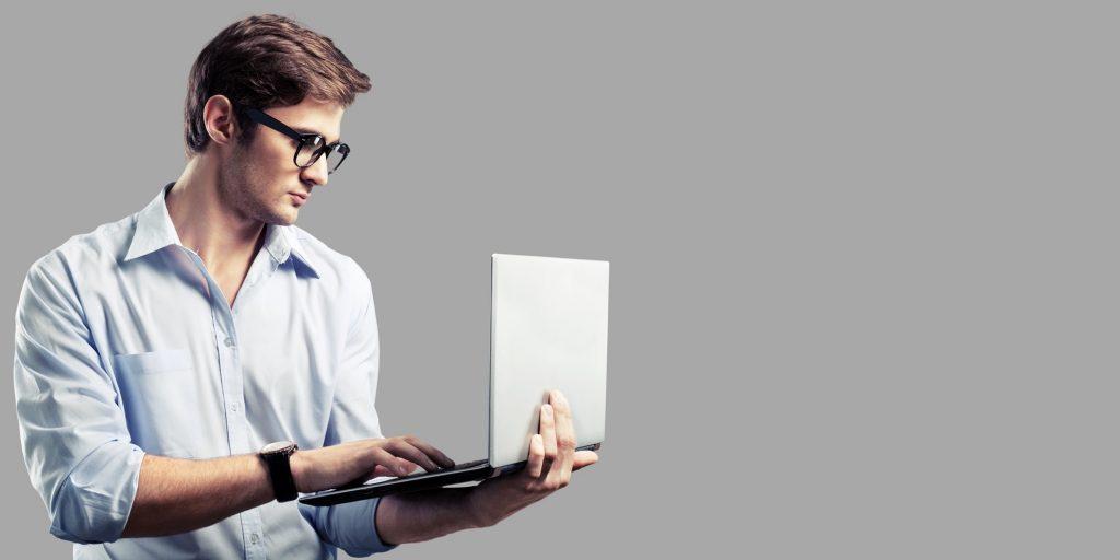 Hombre con camisa, lentes y reloj sosteniendo su laptop con una mano y escribiendo con la otra