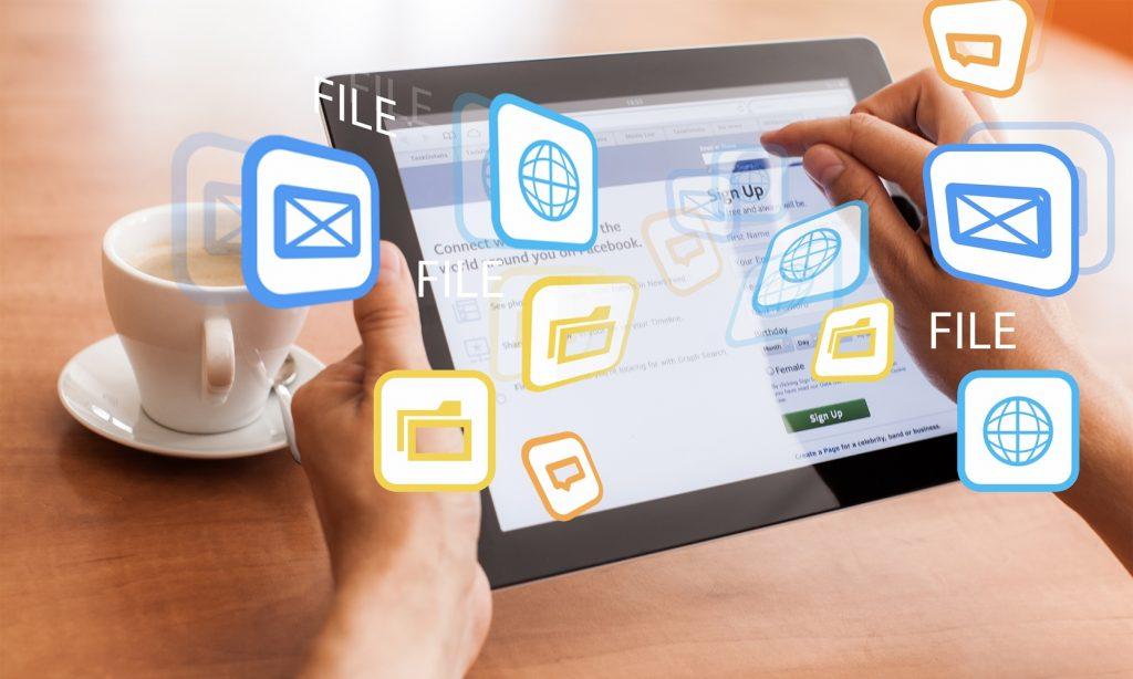 Manos sosteniendo una tablet rodeada de logos virtuales de internet, correo y carpetas