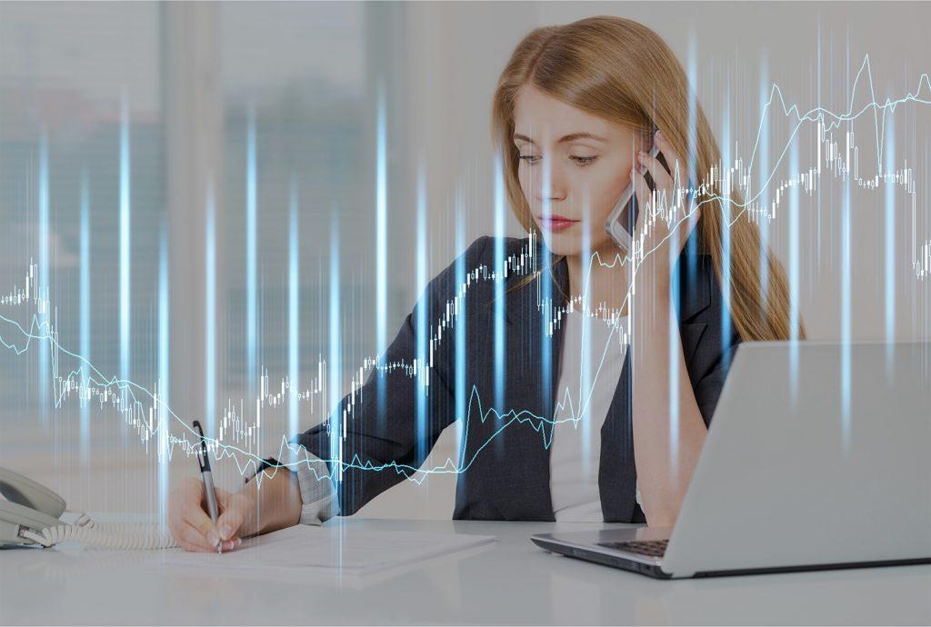 Recepcionista virtual con una laptop mientras anota en una hoja y contesta una llamada telefónica