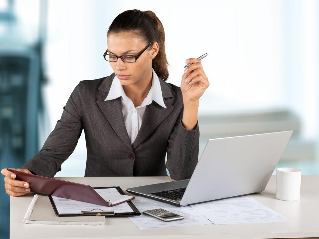 Mujer sentada frente al escritorio con una laptop, un móvil y leyendo una carpeta