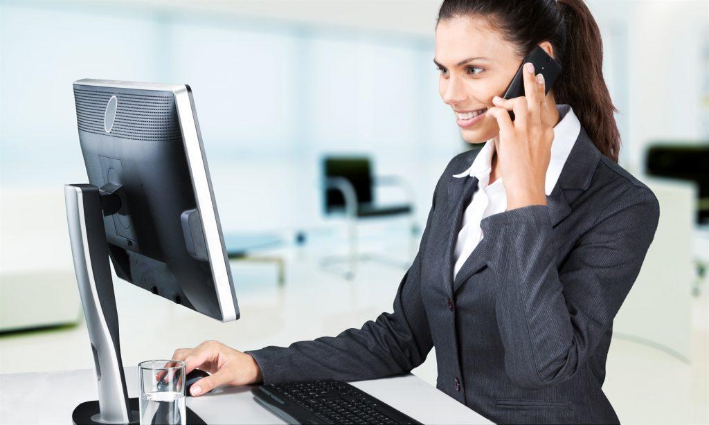 Mujer sentada frente a su laptop contestando una llamada