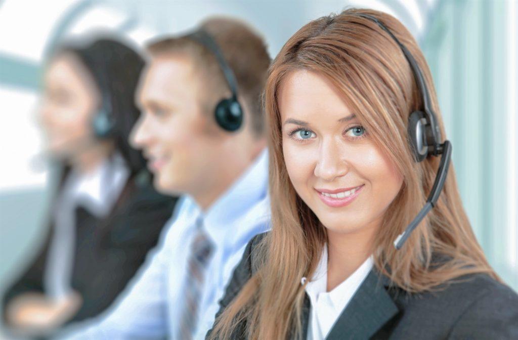 Mujer sonriente con audífonos y micrófonos de call center trabajando con un hombre y una mujer en la oficina
