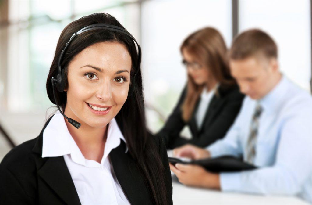 Operadora de customer success con audífonos y micrófono de call center con dos clientes detrás de ella
