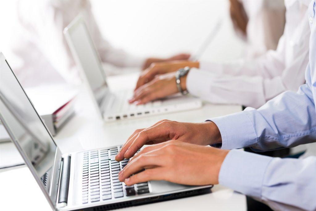 Escritores fantasma trabajando en sus laptops sobre un escritorio