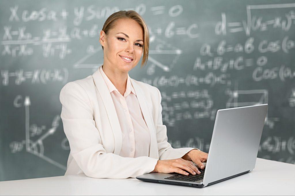 Profesora virtual frente a una pizarra con fórmulas matemáticas ante una laptop