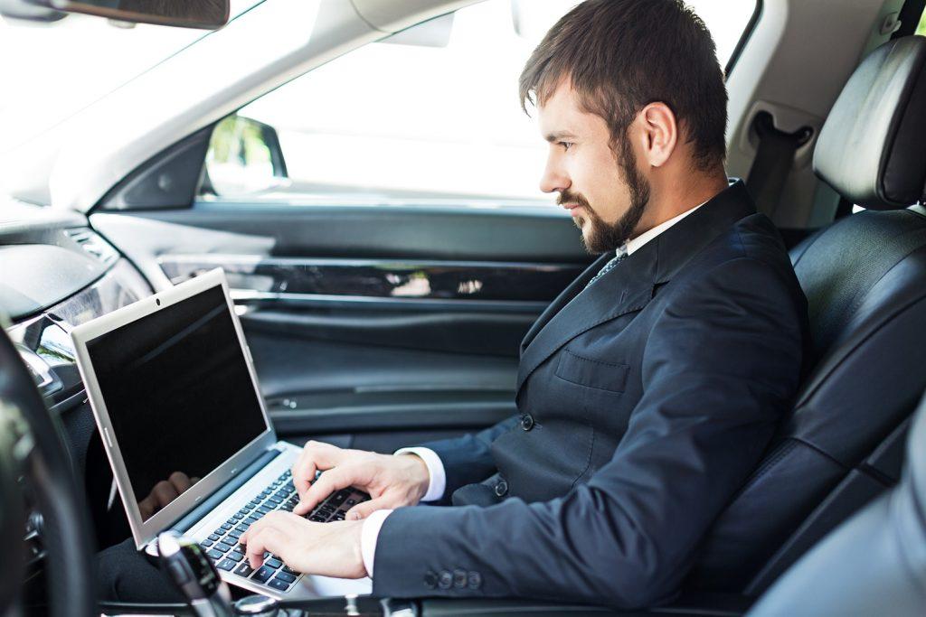 empleado virtua de relaciones públicas sentado en su aotomóvil trabajando desde su laptop personal